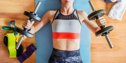 The girl is holding two dumbbells in her hands and lying on the blue mat