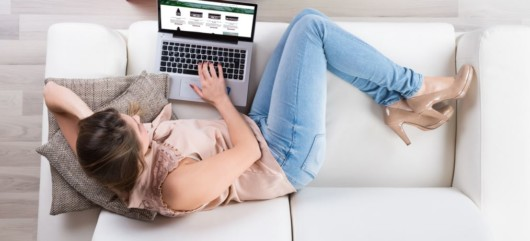 The girl in light blouse, jeans and light heels is lying on the white sofa with the laptop looking for cbd products