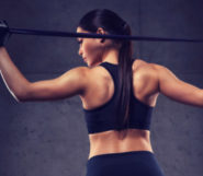A fit girl is standing with her back holding a resistance band over her shoulders on the dark background
