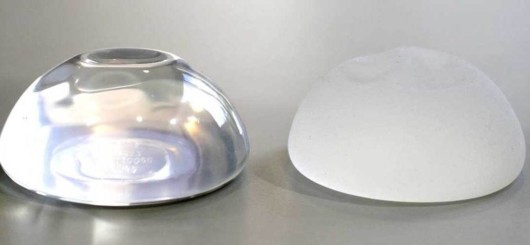 Saline and silicon breast implants on the grey background