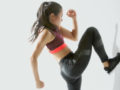 A fit and sexy girl is doing exercise against a white wall