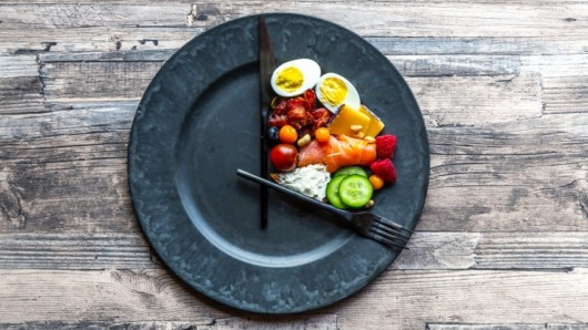 A black plate with food on is shows the eating window of intermittent fasting