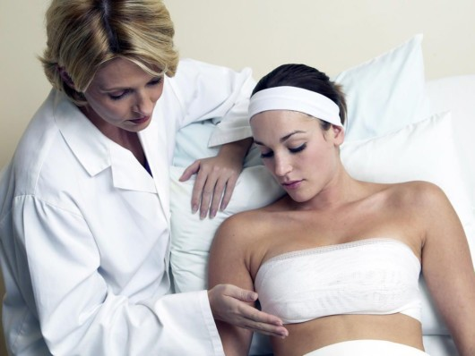 Doctor is checking how the girl who did breast reduction operation is recovering