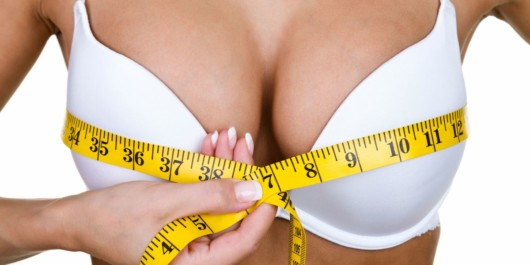 girl with big breast and white bra on white background is measuring her breast before breast reduction surgery