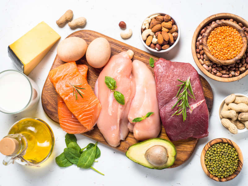 Lean protein: chicken, beaf, salmon, nuts, avocado, lentils, eggs on wooden cutting board and white background