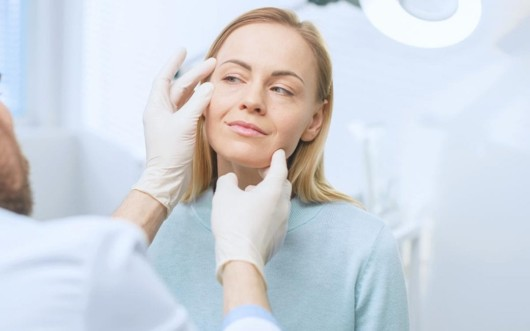 A woman has a  follow-up appointment with the doctor after the facelift procedure