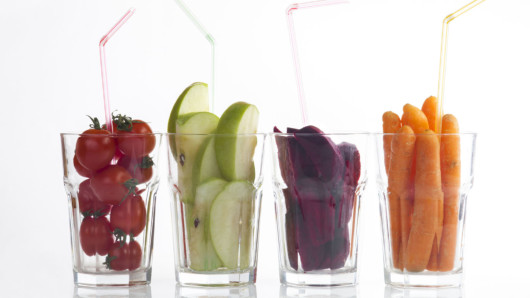 Four glasses filled with tomatoes, green apples, beetroot and carrots on white