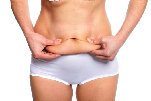 A close up photo of a girl on white that pinches her belly post-Ppegnancy fat