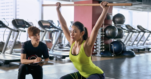 A personal trainer is checking the technique of her client white she is performing overhead squat