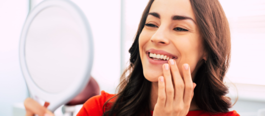 A beautiful girl is looking in the mirror, smiling an checking her dental implants