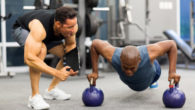 A personal trainer is motivating his client who is doing push ups on kettlebells