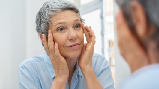 An elderly woman in blue blouse is looking into the mirror and touching her face checking age related blemishes