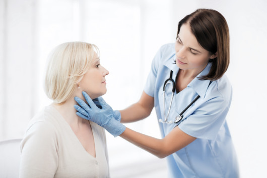 A woman doctor is checking woman's throat in a walk-in clinic