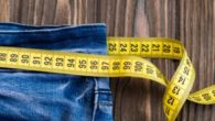 jeans with a tape measure on wooden background