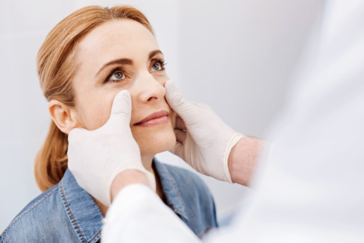 A doctor is checking woman's face before the plastic or cosmetic surgery
