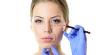 A doctor is putting marks on the young girl's face before plastic surgery