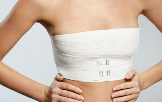 An isolated girl's body on white who is standing in gauze and compression garments after  breast reconstruction surgery