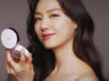 A close up picture of a beautiful Korean girl with a perfect skin on dark background who looks into the mirror