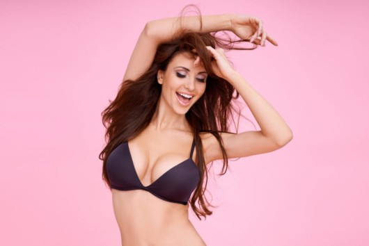 A beautiful girl in a black bra on pinky background showing her augmented breasts