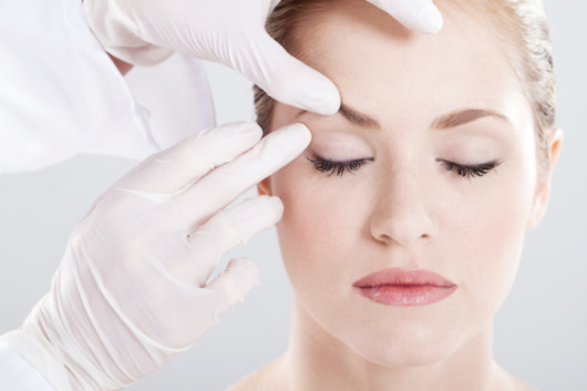 A close up face of a beautiful girl on white background and doctor's hands in white gloves