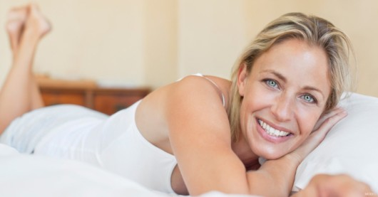 A happy woman lying on the bed and smiling.