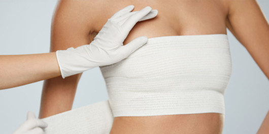 A close up photo of girl's breast in a bandage after the breast augmentation procedure