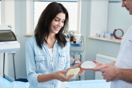 A girl checks the breast implants before breast augmentation