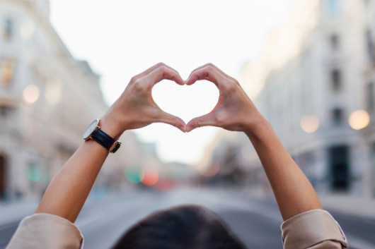 A girl put her arms in the air and holds her fingers in the shape of heart
