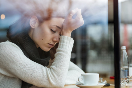 Girl in white sweater sitting in the cafe with a headache.