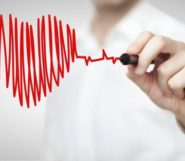 A doctor is drawing a red heart with a pen in front of him