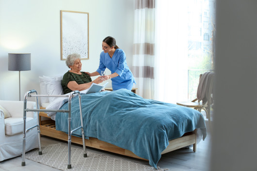 A nurse is helping an old lady and giving her water in hospice
