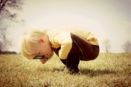 A little boy with a hand lens bent over the ground and looking at something
