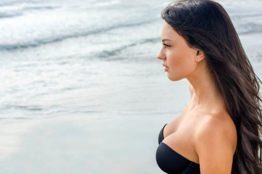 A A beautiful girl with augmented breast is on the beach and looking into the distance