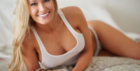 A beautiful and young girl in a white undershirt lying on the bed and smiling