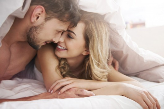 A man and a woman are lying in bed under the cover and embracing
