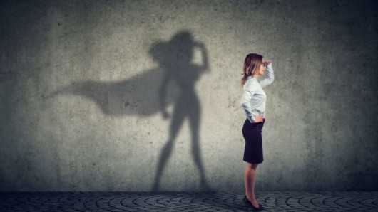 A woman is standing in front of the wall feeling non confident and her with her shadow as a wonder woman