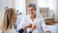 A health care nurse is helping the old lady to dress at home