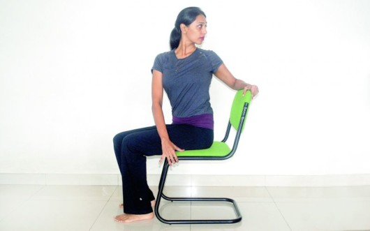 Girl is sitting on the chair and doing chair rotations exercise for back