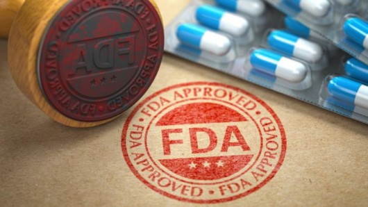 blue and white pills and red FDA stamp on the brown background