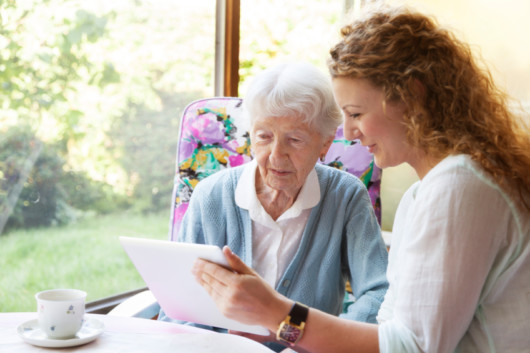 Young girl is showing something to an old woman and choosing an aged care home