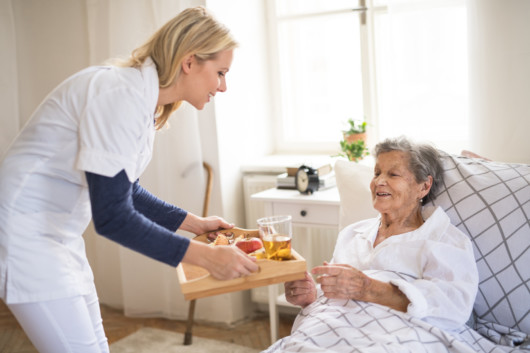A home healthcare nurse is helping an old lady with breakfast. She is serving it to bed