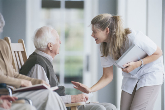 Caretaker is talking nicely to an old man in an aged care home