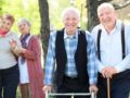 Old people are walking in the park and look happy.