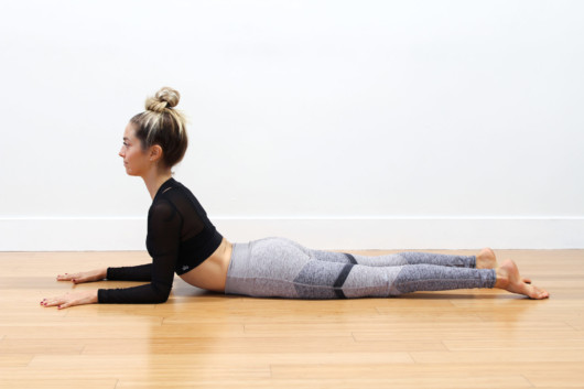 Girl is lying on the floor and doing sphinx pose to get rig of back pain