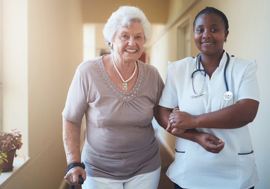 A home nurse is helping the old lady to walk. They are both smiling
