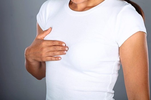 Girl in white t-shirt covers one breast with a hand