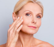 Middle aged woman isolated on white showing her young skin after invasive treatments
