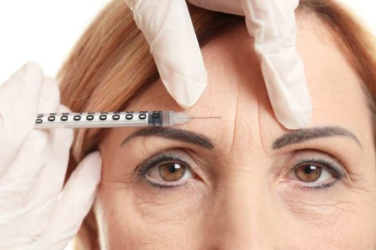 A middle age woman with face wrinkles is doing botox treatment