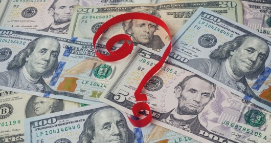 A red question mark on top dollar banknotes