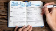 A guy is making a meal plan and writes it in the notebook that lies on wooden background
